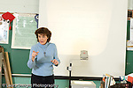 Education Elementary female science specialist using overhead transparency projector to explain concept to class  pointing calling on student (not visible) horizontal
