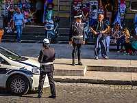 Urban Street Photography. Near the Vatican, in Rome Italy. <br /> The strong warm lighting that was falling on the  Police Officers created the experience of this photograph. I liked the mix of the dark shadows and the bright sunlight that created the mood of this photograph.  The people, the cars, and the scooters, added further interest and action to this photograph.