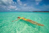 Maldives, Rangali Island. Conrad Hilton Resort. Woman swimming in the ocean. (MR)