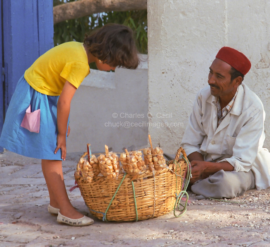 Tunisia, Sidi Bou Said.  Girl Buying Cookies, Biscuits, from Man Wearing a Chechia, a Traditional Tunisian Hat.