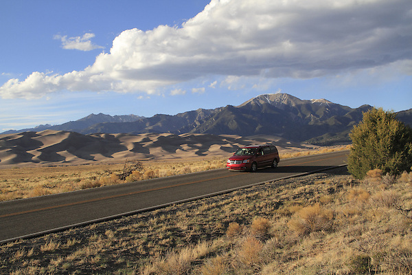 Red van on highway exiting Great Sand Dunes National Park, Colorado. John offers private photo trips to Great Sand Dunes National Park and all of Colorado. All year long.