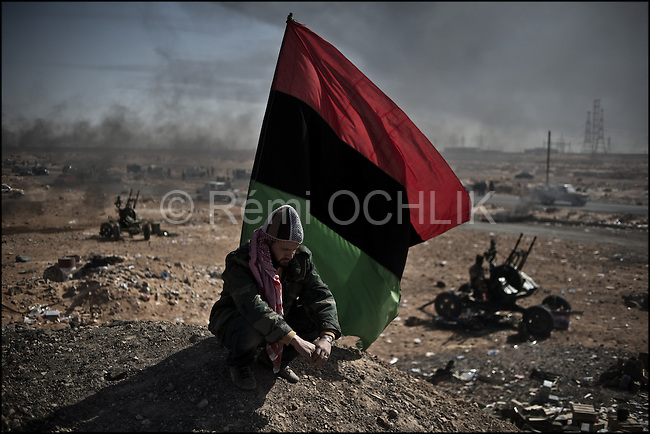 © Remi OCHLIK/IP3 -   RAS LANOUF March 11, 2011 - An opposition fighter rest under a rebellion flag in the middle of the battle field of oil town Ras Lanouf..Opposition forces fight troops of colonel Muamar Gadhafi on a road just outside the strategic oil town of Ras Lanouf, Libya..Loyalist forces bombed the rebels from the air and the ground. At least five oppositin fighters were killed and fifteen injured
