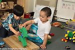 Education preschool block area 3-4 year olds two boys playing together building