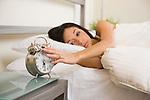 USA, Illinois, Metamora, Young woman turning off alarm clock