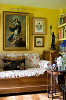 A Murillo inspired copy of the Madonna hangs above a traditional wooden day bed with floral pattern cushions in a sitting room idecorated in a deep yellow.