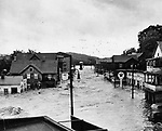 View of the South Main Street in Naugatuck while the flood waters were at their crest. Note three men on the porch roof of the building at right.