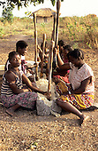 Lake Chaya, Zambia. Young women sitting round a trough pounding yams with pestle sticks.