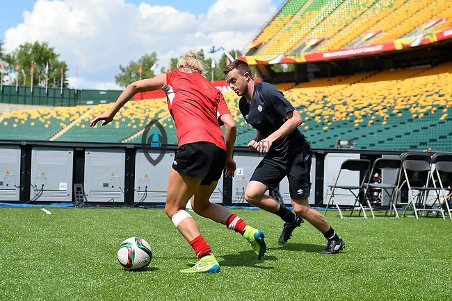 Canada's Lauren Sesselmann and Assistant Coach Andrew Peat perform drills  before team practice on the eve of inaugural Women's World Cup Soccer match, Thursday June 04, 2015 in Edmonton, Alberta. (Mo Khursheed/TFV Media via AP Images)