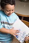 Education Preschool 4-5 year olds proud boy explaining his drawing art activity recognizable human figures vertical