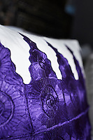 A detail of an embroidered purple and white pillow.