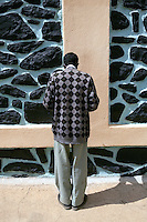 Eritrea. Maekel province. Asmara. St Michael church. A black man is praying on St Michael's day during an orthodox religious service. He is standing alone in front of a wall. Black stones.  © 2006 Didier Ruef