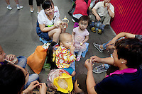 China. Shanghai. World Expo. Expo 2010 Shanghai China.  China Pavilion. A family, all chinese tourists, seats and rests on the ground. A young child eats a yoghurt, while his sister eats an egg. Baby's feeding bottle. 25.06.10 © 2010 Didier Ruef