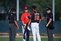 AZL Angels manager Dave Stapleton meets with AZL D-backs manager Wellington Cepeda (50) and umpires Sam Clark (left) and Tyler Wall (right) before an Arizona League game on July 20, 2019 at Salt River Fields at Talking Stick in Scottsdale, Arizona. The AZL Angels defeated the AZL D-backs 11-4. (Zachary Lucy/Four Seam Images)