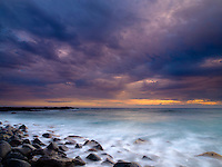 An amazing sunset from Wawaloli Beach Park after Hurricane Iselle hit the Big Island and downgraded to a tropical storm. Waves mingle with large boulders and black sand along the shoreline.