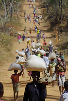 A man walks past thousands of other displaced people after receiving food at a relief center outside Kuito, Angola, Friday, June 14, 2002. Humanitarian groups say the April cease-fire in the long civil war between the Angolan government and UNITA rebels has allowed people who had been trapped by fighting to seek food and medical care in the cities and at aid centers. Nearly three decades of civil war have left much of the country in ruins, and the United Nations says up to a half million people face starvation..Photo/Marcelo Hernandez