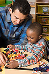 Education Preschool 2-3 year olds therapist or intern working with boy in classroom year olds