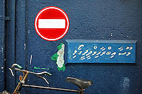 'One Way' street sign above a parked bicycle, Malé , Maldives.
