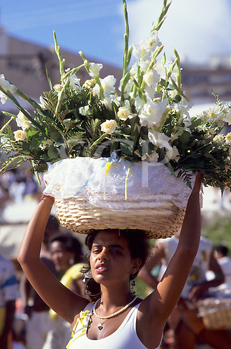 Salvador, Bahia, Brazil. Woman carrying offering of white flowers in a basket on her head; Festival of Iemanja.