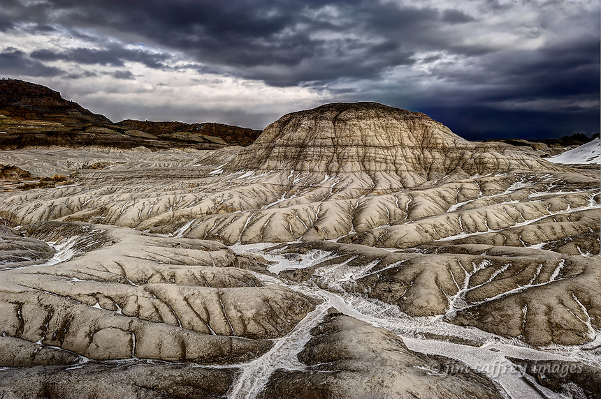 A lone hill in the Mesa de Cuba Badlands with deeply etched erosion channels under a stormy sky.