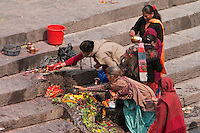 Pashupatinath Temple, Nepal.  Family Members Offer Prayers and Food Offerings for the Deceased on the Bank of the Bagmati River.