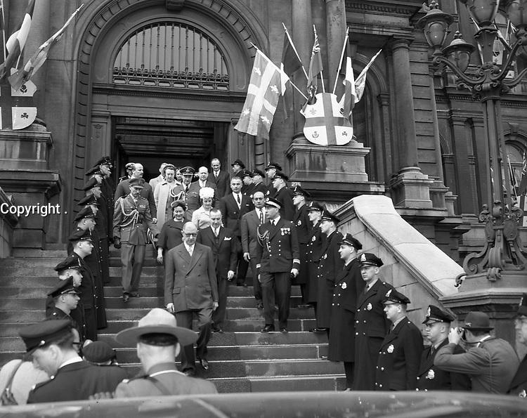 Le general  Charles de Gaulle descendant les marches extérieures de l'hotel de ville suivi du maire Sarto Fournier et de leurs epouses. On y voit une haie d'honneur de policiers de la Ville de Montréal de même que les drapeaux ornant l'entrée principale de l'hôtel de ville.21 avril 1960