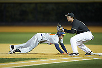 Cam McDonald (29) of the Illinois Fighting Illini dives back towards first base as Bobby Seymour (3) of the Wake Forest Demon Deacons waits for a pick-off throw at David F. Couch Ballpark on February 16, 2019 in  Winston-Salem, North Carolina.  The Fighting Illini defeated the Demon Deacons 5-2. (Brian Westerholt/Four Seam Images)