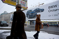 Pedestrians on Tverskaya, the main street in Moscow, in front of BMW billboard advertising.. .Picture by Justin Jin.