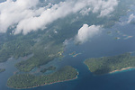 Rendova Island, Solomon Islands; an aerial view of the fringe islands surrounding Rendova with clouds overhead in the late morning