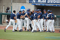 Grayson Chapman (8) of the Wingate Bulldogs is surrounded by his teammates as he walks to the dugout after his pinch-hit double drove in a run against the Central Missouri Mules during the 2021 DII Baseball National Championship at Coleman Field at the USA Baseball National Training Complex on June 12, 2021 in Cary, North Carolina. The Bulldogs defeated the Mules 5-3. (Brian Westerholt/Four Seam Images)