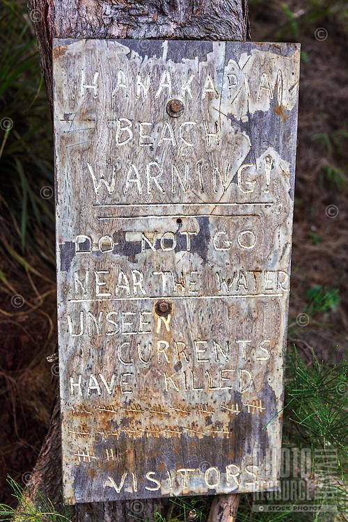 A sign along the Kalalau Trail warning hikers about dangerous currents at Hanakapi'ai Beach, Kaua'i.