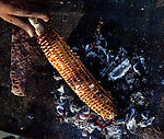 June 21 2012, New Delhi, India:  A man cooks corn on the cob underneath India Gate. It is the national monument of India. Situated in the heart of New Delhi, India Gate was designed by Sir Edwin Lutyens. Originally known as All India War Memorial, it is a prominent landmark in Delhi and commemorates the 90,000 soldiers of the British Indian Army who lost their lives while fighting for the British Indian Empire, or more correctly the British Empire in India British Raj in World War I and the Third Anglo-Afghan War. It is composed of red sand stone and granite.        Picture by Graham Crouch/Holland Herald