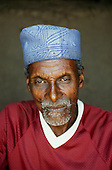 Mikumi, Tanzania; old man with short grey beard wearing a blue hat and a red shirt.
