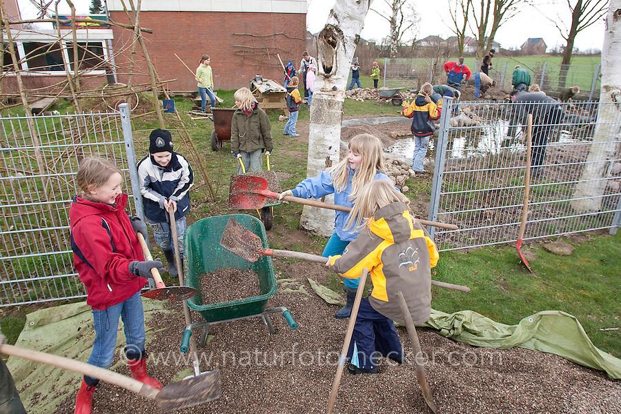 Grundschulklasse, Schulklasse legt einen Schulteich, Schul-Teich, Teich, Gartenteich, Garten-Teich im Schulgarten an, Kinder und Eltern laden feinkörnigen Kies in Schubkarren, der als Bodensubstrat für den neuangelegten Teich dient