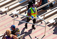 Nov 1, 2020; Las Vegas, Nevada, USA; A track employee cleans handrails as NHRA fans watch racing from the grandstands during NHRA Finals at The Strip at Las Vegas Motor Speedway. Mandatory Credit: Mark J. Rebilas-USA TODAY Sports