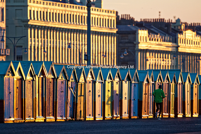 A man jogs past the coloured beach huts at the Brighton seafront a freezing cold but clear morning  in East Sussex, England UK. Saturday 24 February 2018