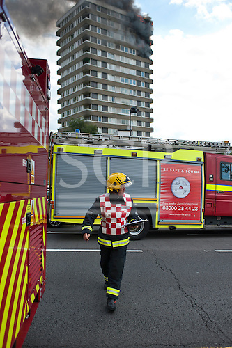 Kingston upon Thames, England. Fireman and two fire engines with a tower block of flats on fire behing.