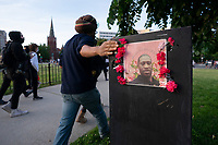 A demonstrator touches a memorial to George Floyd during a protest in Washington, D.C., U.S., on Monday, June 1, 2020, following the death of an unarmed black man at the hands of Minnesota police on May 25, 2020.  More than 200 active duty military police were deployed to Washington D.C. following three days of protests.  Credit: Stefani Reynolds / CNP/AdMedia