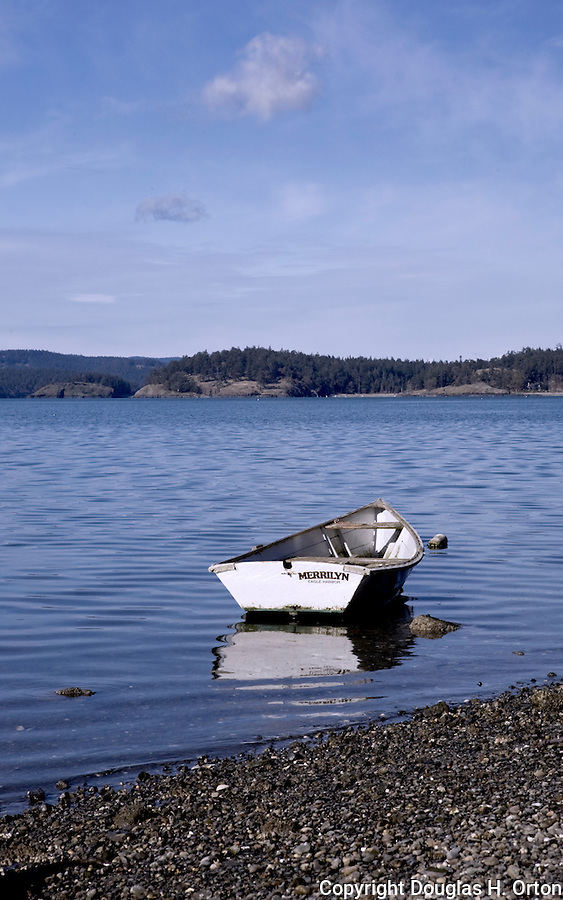 A wooden rowing dinghy floats on mooring near shore.  Lopez Island, Washington.  Lopez, nicknamed Slopez for its laid back lifestyle, is in Washington State's San Juan Islands group.  Decateur, Obstruction, and Orcas Islands lie in the background.