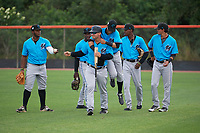 Miami Marlins Victor Mesa Jr. jumps on coach Nathan Mikolas, in front of (L-R) Albert Guaimaro, Milton Smith II, Daniel Paulino, and Jorge Caballero after a meeting during warmups before a Minor League Extended Spring Training game against the New York Mets on April 12, 2019 at First Data Field Complex in St. Lucie, Florida.  (Mike Janes/Four Seam Images)