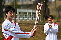 25th March 2021, Fukushima, Japan;  Japanese high school student Asato Owada holds the torch on the first day of the Tokyo 2020 Olympic torch relay in Futaba, Fukushima of Japan, on March 25, 2021.