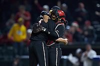 Shay Smiddy (5) of the Louisville Cardinals hugs catcher Zeke Pinkham (11) against the Notre Dame Fighting Irish in Game Eight of the 2017 ACC Baseball Championship at Louisville Slugger Field on May 25, 2017 in Louisville, Kentucky. The Cardinals defeated the Fighting Irish 10-3. (Brian Westerholt/Four Seam Images)