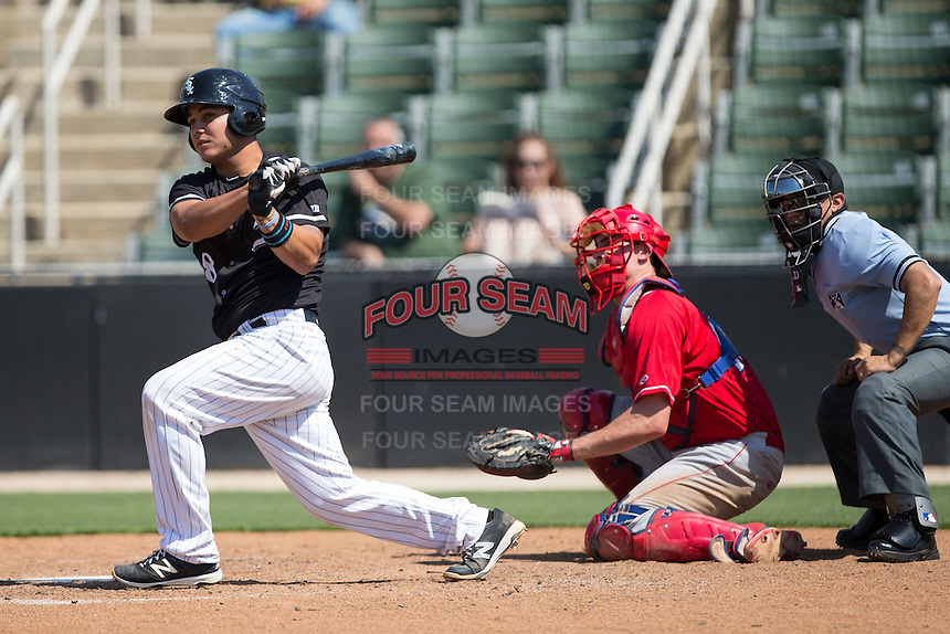 Daniel Gonzalez (8) of the Kannapolis Intimidators follows through on his swing as Lakewood BlueClaws catcher Austin Bossart (17) and home plate umpire David Martinez look on at Kannapolis Intimidators Stadium on May 8, 2016 in Kannapolis, North Carolina.  The Intimidators defeated the BlueClaws 3-2.  (Brian Westerholt/Four Seam Images)