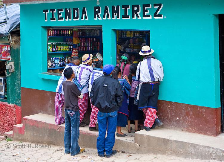 A group of local Guatemalans watch television through a tienda window on the street in Todos Santos Cuchumatan, Western Highlands, Guatemala