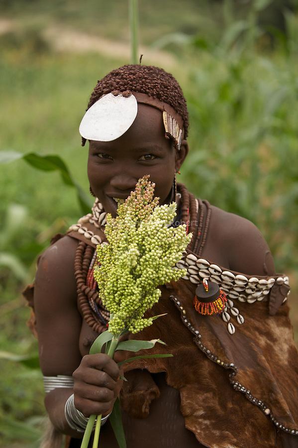 Jeune fille Hamer adans un champ de sorgho.
