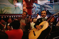 Restaurant patrons join Mariachi bands in song.  Musicians wait to be hired for a song or a party at Plaza Garibaldi. The traditional music is a favorite not just with tourists, but with sentimental Mexicans who may serenade a sweetheart or drown their sorrow in liquor and a song.