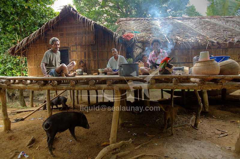 a family having a meal in their local house at  Hessessai Bay at PanaTinai (Panatinane)island in the Louisiade Archipelago in Milne Bay Province, Papua New Guinea.  The island has an area of 78 km2..The Louisiade Archipelago is a string of ten larger volcanic islands frequently fringed by coral reefs, and 90 smaller coral islands located 200 km southeast of New Guinea, stretching over more than 160 km and spread over an ocean area of 26,000 km? between the Solomon Sea to the north and the Coral Sea to the south. The aggregate land area of the islands is about 1,790 km? (690 square miles), with Vanatinai (formerly Sudest or Tagula as named by European claimants on Western maps) being the largest..Sideia Island and Basilaki Island lie closest to New Guinea, while Misima, Vanatinai, and Rossel islands lie further east..The archipelago is divided into the Local Level Government (LLG) areas Louisiade Rural (western part, with Misima), and Yaleyamba (western part, with Rossell and Tagula islands. The LLG areas are part of Samarai-Murua District district of Milne Bay. The seat of the Louisiade Rural LLG is Bwagaoia on Misima Island, the population center of the archipelago.PanaTinai (Panatinane) is an island in the Louisiade Archipelago in Milne Bay Province, Papua New Guinea. The island has an area of 78 km2..The Louisiade Archipelago is a string of ten larger volcanic islands frequently fringed by coral reefs, and 90 smaller coral islands located 200 km southeast of New Guinea, stretching over more than 160 km and spread over an ocean area of 26,000 km? between the Solomon Sea to the north and the Coral Sea to the south. The aggregate land area of the islands is about 1,790 km? (690 square miles), with Vanatinai (formerly Sudest or Tagula as named by European claimants on Western maps) being the largest..Sideia Island and Basilaki Island lie closest to New Guinea, while Misima, Vanatinai, and Rossel islands lie further east..The archipelago is divided into the Local Leve