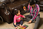 12 month old baby girl sitting on floor playing toy xylophone making music with mother