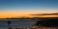 Nice Aerial sunset view, with the old town and lit-up airport area under a colorful clear sky above Angels Bay, French Riviera (Côte d'Azur), France