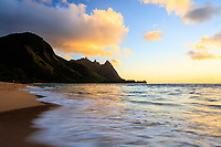 The frothy surf reflects the gold and blue sky at sunset at Tunnels Beach, Kaua'i.