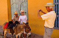 Tourists taking photo of old man riding donkey for tourists in the old colonial city of Trinidad in Cuba